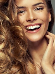 Happy blonde woman with copy space for your text isolated on gre